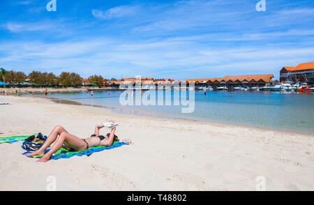 A teenage girl sunbathing and reading a book on the beach at Sorrento Quay Hillarys Boat Harbour. - Stock Photo