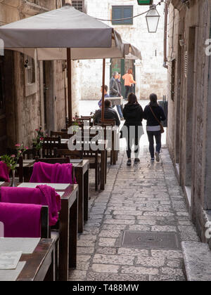 Dubrovnik, Croatia - april 2019: Old City of Dubrovnik. Outdoor restaurant in one of the narrow streets of medieval town - Stock Photo