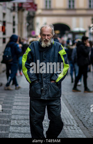 A homeless man covered in drool and dirt walks through the streets of Prague on a cold spring day - Stock Photo
