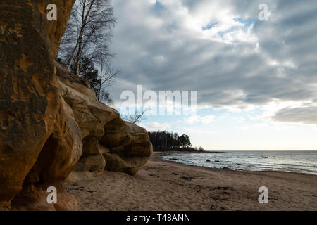 Limestone beach at the Baltic Sea with beautiful sand pattern and vivid red and orange color - Tourist writings on the walls and rocks and sand - - Stock Photo