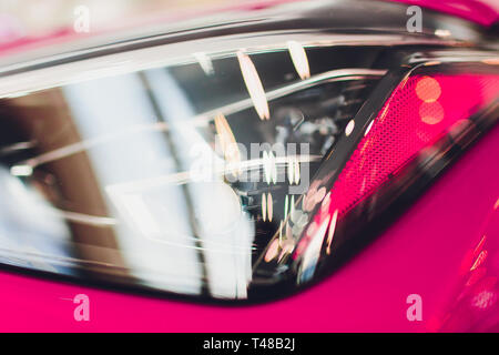Close up shot headlight in luxury pink car background. Modern and expensive sport car concept. - Stock Photo