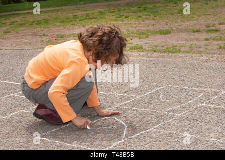 Little girl drawing squares on the street, for hopscotch - Stock Photo