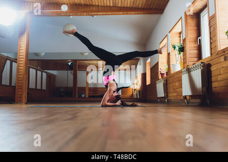 Young yogi attractive woman practicing yoga concept, standing in salamba sirsasana exercise, headstand pose, working out, wearing sportswear, black - Stock Photo
