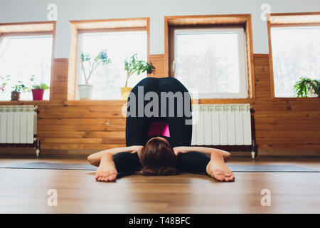 Young sporty attractive woman practicing yoga, doing asana paired with Cat Pose on the exhale exercise, Cow, Bitilasana pose, working out, wearing - Stock Photo
