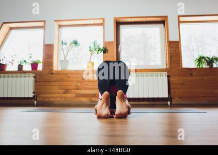 sporty beautiful young woman doing halasana plough pose