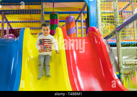 Little boy is going down a slide at the playground. He is laughing and having fun on the jungle gym. Boy riding from childrens slides on playground. - Stock Photo