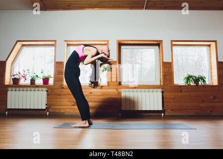 Young woman practicing yoga, doing head to knees, uttanasana exercise, Standing forward bend pose, working out, wearing sportswear, black pants and - Stock Photo