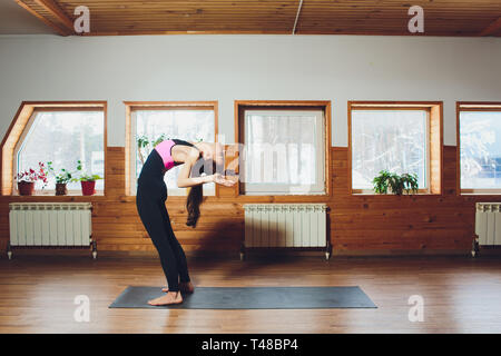 Young woman practicing yoga, standing in variation of head to knees exercise, uttanasana pose with hands behind back, working out wearing sportswear - Stock Photo