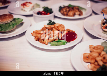 close up. rustic potatoes with sauce and other dishes on the table - Stock Photo
