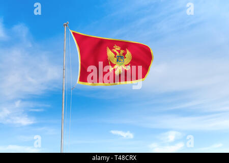 Montenegro flag blowing in the wind over nice blue sky background - Stock Photo