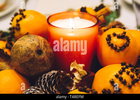 Christmas decoration candle set, with pine cones and oranges decorated with cloves, on a dinner table.