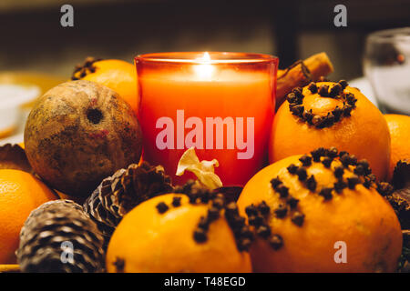 Christmas decoration candle set, with pine cones and oranges decorated with cloves, on a dinner table. Stock Photo
