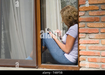 A young pretty woman is sitting on the windowsill and holding a phone in her hand. View from the street. - Stock Photo