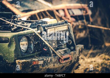 Off Road Expedition. Two Dirty Sport Utility Vehicles Covered by Mud. Motorsport Theme. - Stock Photo