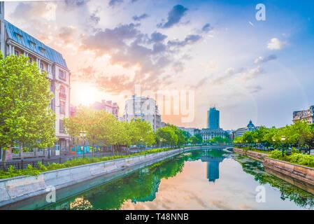 Dambovita river and center of Bucharest at sunset time, Romania. - Stock Photo