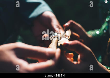 Married couple with traditional wedding dress showing their wedding rings in a dark lighting.selective focus - Stock Photo