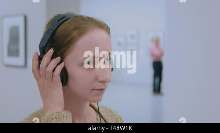 Woman looking at exposition, using headphones and listening audio guide - Stock Photo