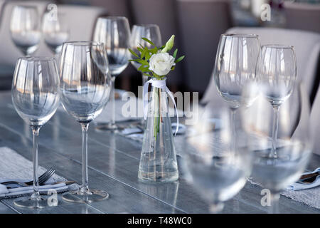Transparent glass vase with bouquet of flowers against background of table setting in modern restaurant. Wine and water glasses stand in row on wooden - Stock Photo