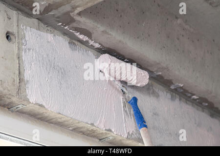 Paint roller and primer on the wall above the window. Concept of repairing houses, apartments, preparing walls for plastering, rough finishing of prem - Stock Photo