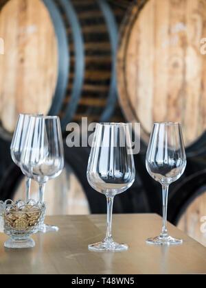 Empty wine glasses in front of wooden wine barrels. - Stock Photo