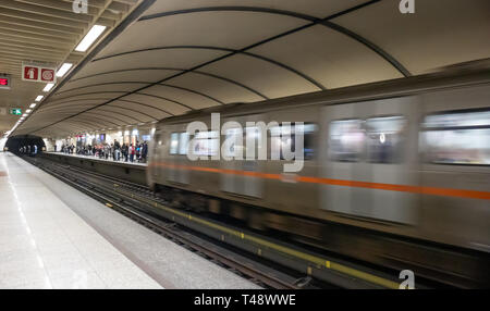 April 14, 2019. Greece, Athens. Metro station at the city center. Blur train in motion entering the station, passengers at the platform waiting to emb - Stock Photo
