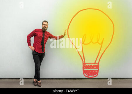 Full length portrait of handsome satisfied bearded businessman in red shirt standing and looking at camera and smiling near turned on big bulb lamp on - Stock Photo