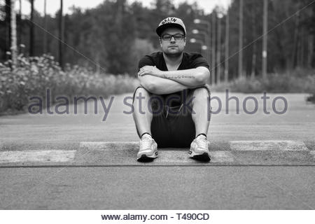 person sits on road - Stock Photo