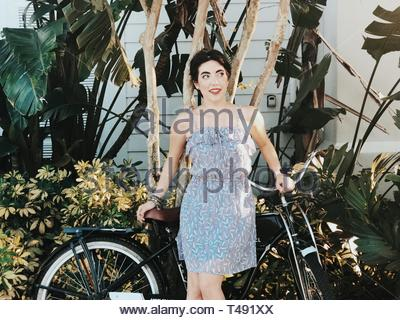 woman wearing gray spaghetti-strap top standing beside the bicycle - Stock Photo