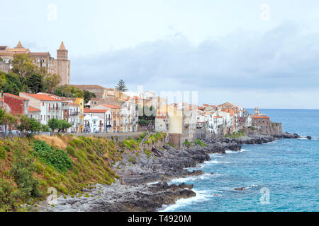 Rocky coast of Sicilian seaside resort of Cefalu with historic houses, cathedral on the hill, promenade . - Stock Photo