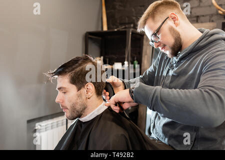 Barber work with clipper machine in barbershop. Professional trimmer tool cuts beard and hair on young guy in barber shop salon. - Stock Photo