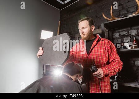 Barber work with clipper machine in barbershop. Professional trimmer tool cuts beard and hair of young guy in barber shop salon. - Stock Photo