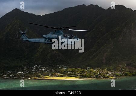 A U.S. Marine Corps AH-1Z Viper attack helicopter with Marine Light Attack Helicopter Squadron 367 conducts a memorial flight April 12, 2019 over Oahu, Hawaii. The flight was in honor of Marine Viper pilots Capt. Brannon and Maj. Matthew M. Wiegand, who were killed in a crash on March 30. - Stock Photo
