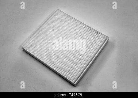 Close-up on a car filter for a white engine as a background with vertical stripes. Spare parts for vehicles, repairs and maintenance. - Stock Photo