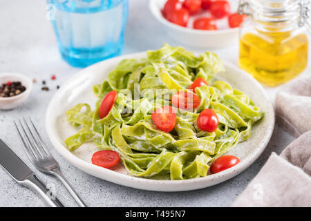 Green spinach pasta with cream sauce and tomatoes on a plate. Italian cuisine food. Closeup view, horizontal orientation - Stock Photo