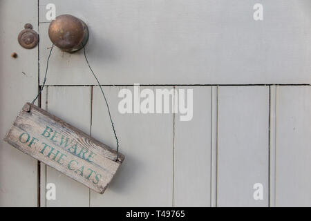 A sign warning to 'Beware of the Cats' on a weathered outside door - Stock Photo