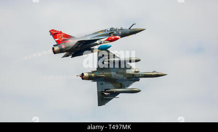 Two Mirage 2000 jets from the French Air Force Armee de l'Air Couteau Delta tactical display team performing a close flying manoeuvre - Stock Photo