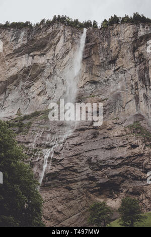 View closeup waterfall Staubbach fall in mountains, valley of waterfalls in national park of Lauterbrunnen, Switzerland, Europe. Summer landscape, sun - Stock Photo