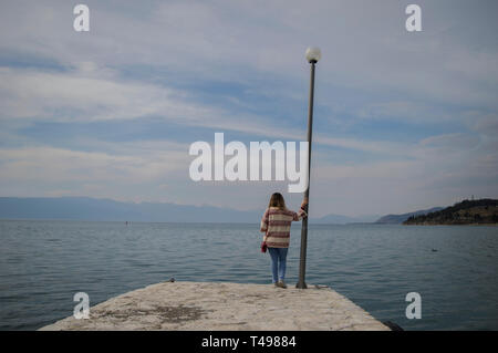 A girl standing at the end of a pier looking at the vast emptiness of a natural lake. - Stock Photo