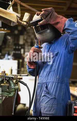 Welder is welding in the garage,industrial Worker labourer at the factory welding steel structure - Stock Photo