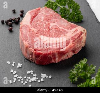 Raw ribeye steak on a slate with juniper berries and parsley. - Stock Photo