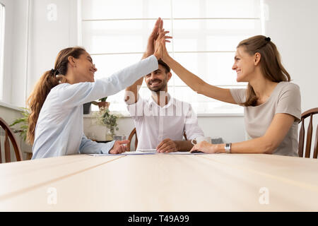 Three partners business team people give high five together - Stock Photo
