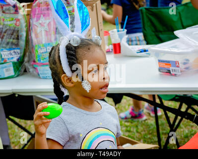 A girl wearing bunny ears holds up a plastic egg during a community Easter egg hunt at Langan Park, April 13, 2019, in Mobile, Alabama. - Stock Photo