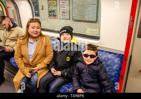 A mother and her young sons pose for a portrait onboard a London Underground train on a family day out. - Stock Photo