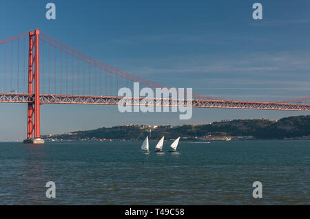 Three small sailing boats at the Tagus River with the 25 of April bridge on the background in the city of Lisbon, Portugal - Stock Photo