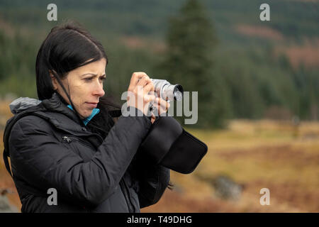 Young woman taking pictures in the wilderness - Stock Photo