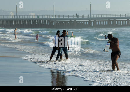 Durban, KwaZulu-Natal, South Africa, couple wading in surf, people swimming in sea, North Beach, landscape, city, holiday - Stock Photo