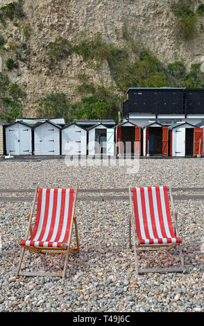 Two red and white striped deckchairs on the shingle harbour beach of Beer in Devon (UK) with a row of beach huts in the background. - Stock Photo