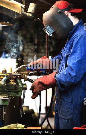 welder is welding metal part in garage. with protective mask, industrial steel welder - Stock Photo