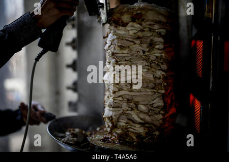 FRESH Shwarma made on the grill and grill man is cutting the Shwarma to serve. - Stock Photo