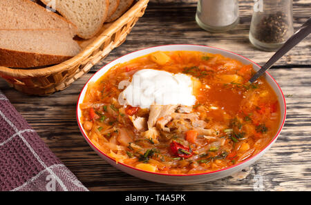 Ukrainian borscht and a spoon of sour cream in a white porcelain plate, a basket with sliced bread and a wafer napkin on an old wooden table - Stock Photo